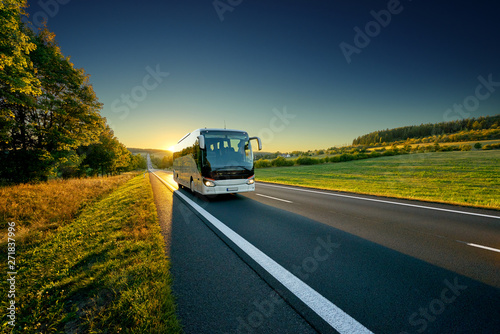Canvas Print White bus traveling on the asphalt road around line of trees in rural landscape