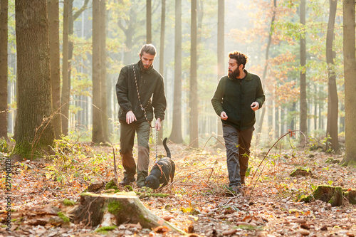 Photographie Zwei Jäger mit einer Bracke als Jagdhund im Wald