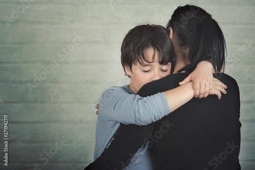 Fototapeta Sad child hugging his mother