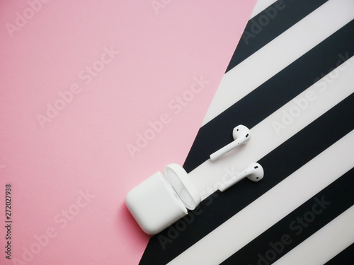 Fotografia White headphones with box case on black and pink background