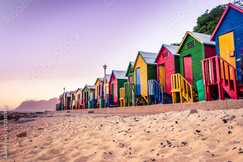Fototapeta premium Widok na piękny zachód słońca nad False Bay z Kalkbay z małymi kolorowymi domkami na plaży, z górami w tle, Kapsztad, RPA
