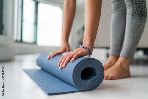Yoga at home woman rolling exercise mat in living room of house or apartment condo for morning wellness yoga practice.