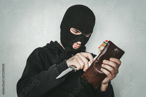 Carta da parati Masked criminal at the black background grins looking at the viewer and showing a purse in hand
