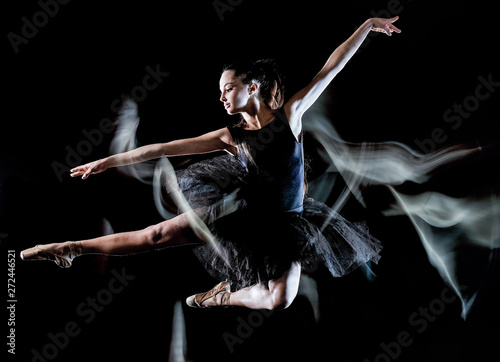 Leinwand Poster one caucasian young woman ballerina dancer dancing isolated on black background