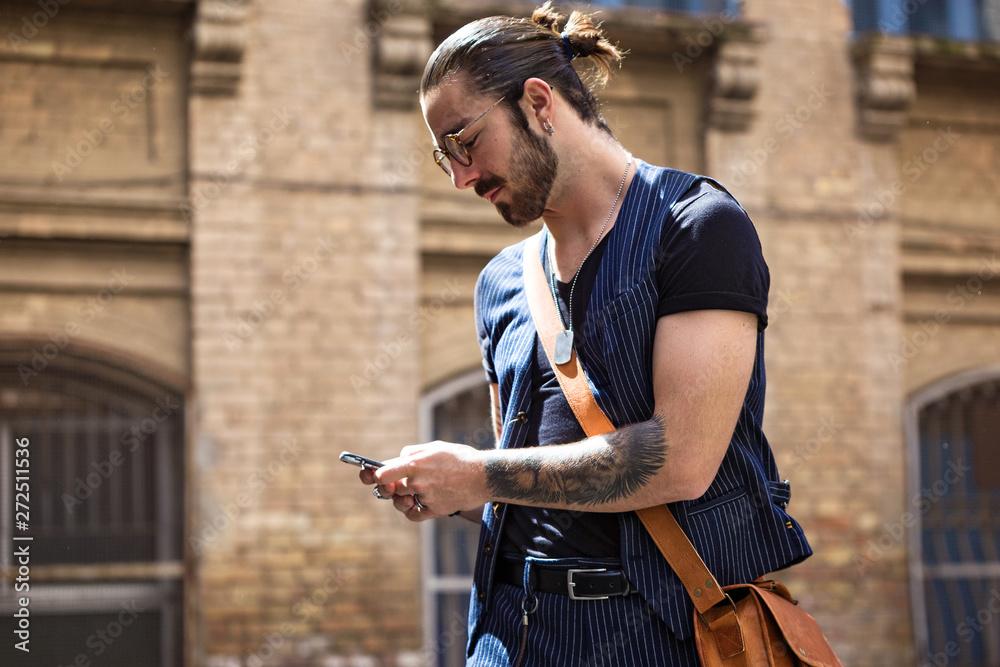 Bearded hipster in glasses using mobile phone.