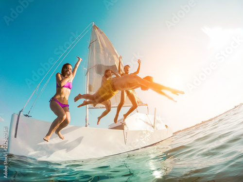 Obraz na płótnie Happy crazy friends diving from sailing boat into the sea - Young people jumping