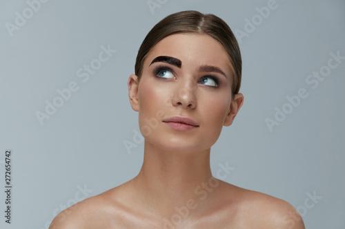 Beauty makeup. Woman coloring eyebrow with brow gel tint Fototapeta