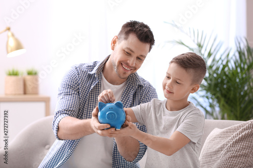 Photo Family with piggy bank and money at home