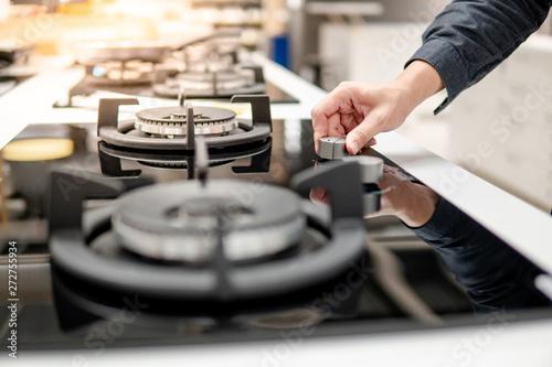 Fotografija Male hand turning switch knob on modern gas stove in kitchen showroom
