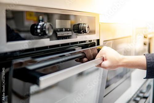 Fotografie, Tablou Male hand opening oven door in the kitchen showroom