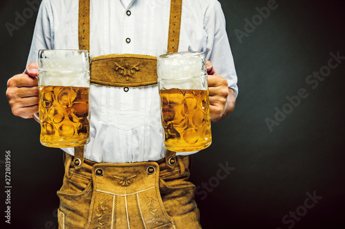 Man in traditional bavarian clothes holding mug of beer Fototapete