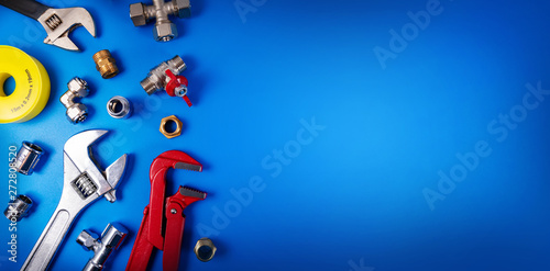 Fotografija plumbing tools and fittings on blue background with copy space
