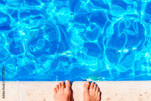 Carta da parati Feet of barefoot man on the edge of a pool about to jump and take a dip in the water to cool off in summer