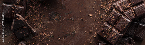 Photo Panoramic shot dark chocolate bar with chocolate chips on metal background