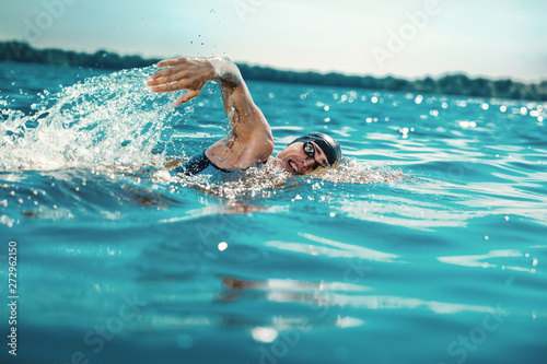 Canvas Print Professional triathlete swimming in river's open water