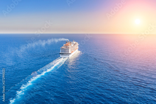 Cruise ship liner goes into horizon the blue sea leaving a plume on the surface of the water seascape during sunset Fototapet