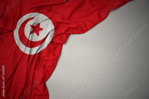 Fototapeta waving national flag of tunisia on a gray background.