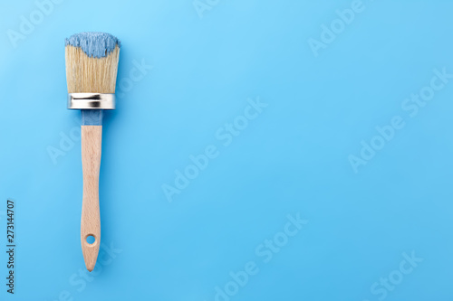 Brush tool in blue paint on blue background, copy space Fototapeta