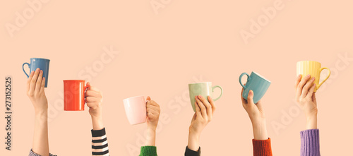Fotografija Many different arms raised up holding coffee cup
