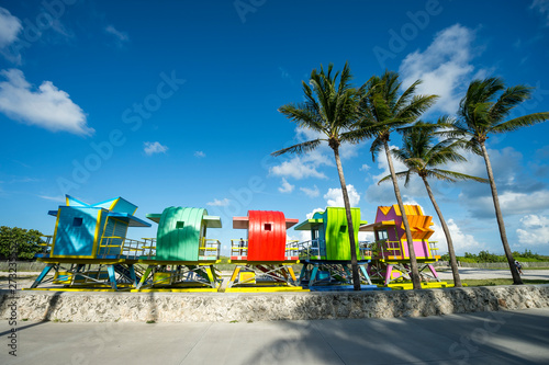 Valokuvatapetti Colorful scenic morning view of brightly painted lifeguard towers with coconut p