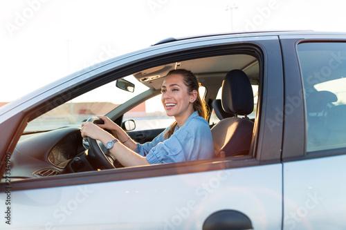 Billede på lærred Happy woman driving a car and smiling