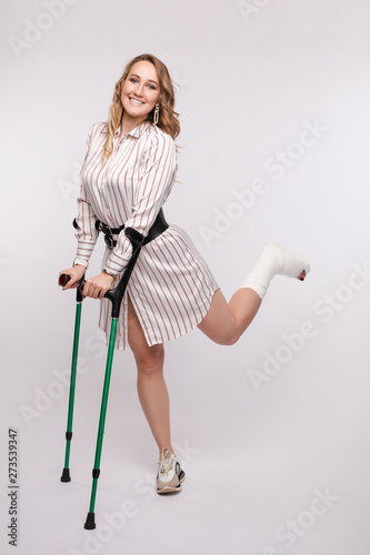 Leinwand Poster Front view of happy woman with broken leg in bandage standing on crutches on isolated background