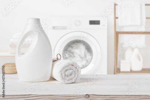 Fototapeta Plain detergent bottle on wood over defocused laundry room interior