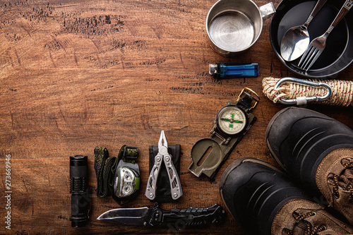 Slika na platnu Outdoor travel equipment planning for a mountain trekking camping trip on wooden background