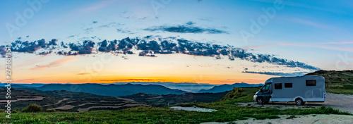 Fotografija Wohnmobil auf einem Hügel bei Sonnenaufgang.