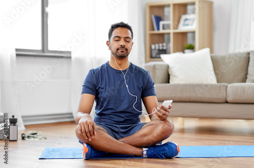 sport, technology and healthy lifestyle concept - indian man in earphones listening to music on smartphone at home