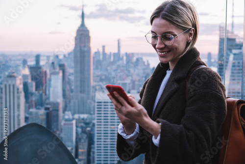 Obraz na płótnie Smiling caucasian female using application in roaming on mobile phone while standing on Observation deck viewpoint with Empire State view building during vacations