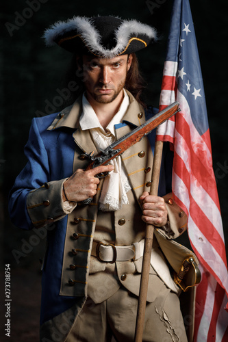 Portrait of man dressed as soldier of War of Independence United States aims from pistol with flag Fototapete