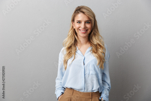 Photo of happy blond businesswoman with long curly hair smiling and standing wit Fototapete