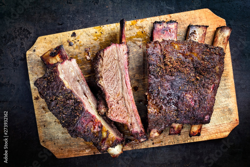 Obraz na plátně Barbecue chuck beef ribs with hot rub as top view sliced on a wooden cutting boa
