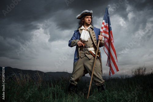 Photographie Man in United States War of Independence soldier costume with flag posing in forest