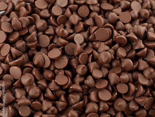 Fototapeta Chocolate morsels spread from top isolated on white background