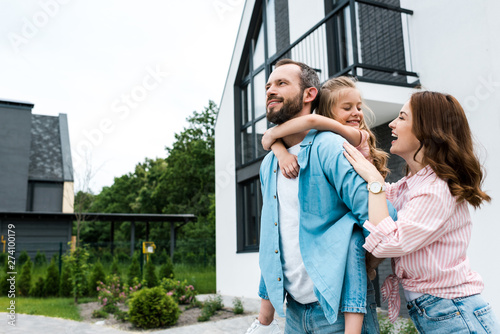 happy man piggybacking daughter near cheerful wife and house