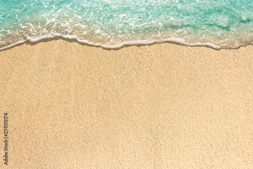 Photo Soft waves with foam of blue ocean on the sandy beach