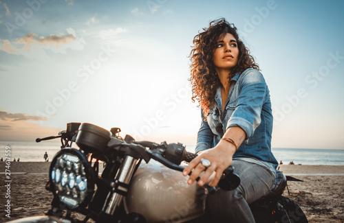 Photo Beautiful girl having fun driving her custom cafe racer motorcycle, enjoying the