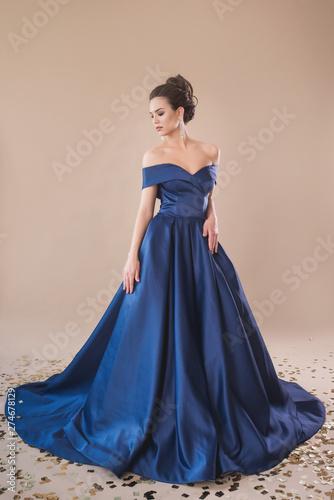 Beautiful girl in evening elegant dress posing on paper beige studio background Fototapet