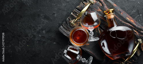 Stampa su Tela A bottle of cognac and glasses on a black background