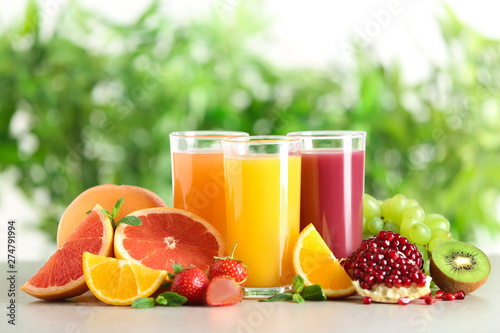 Photo Three glasses with different juices and fresh fruits on table against blurred ba