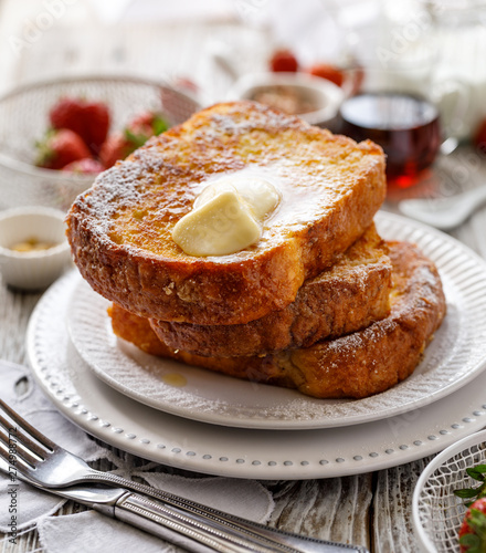 Foto French toast, warm French toast made of sliced brioche with fresh butter, sprinkled with powdered sugar