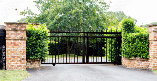 Foto Black metal driveway property entrance gates set in brick fence with garden shru
