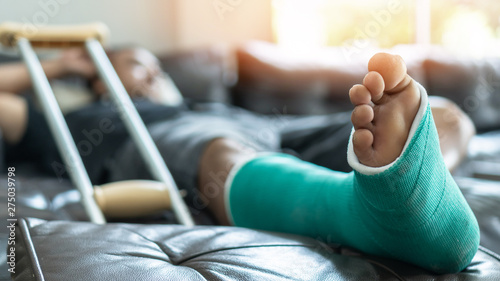 Valokuva Bone fracture foot and leg on male patient with splint cast and crutches during