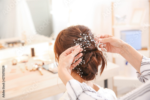 Foto Professional hairdresser working with young bride at home