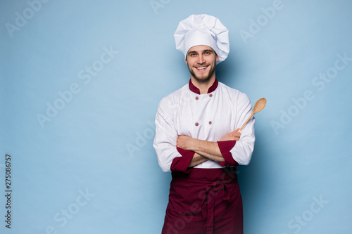 Portrait of positive toothy chef cook in beret, white outfit having tools in crossed arms looking at camera.