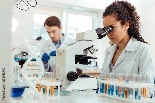Fototapeta Smart female biologist looking into the microscope