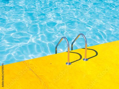 Carta da parati Grab bars ladder in the blue swimming pool. 3d render