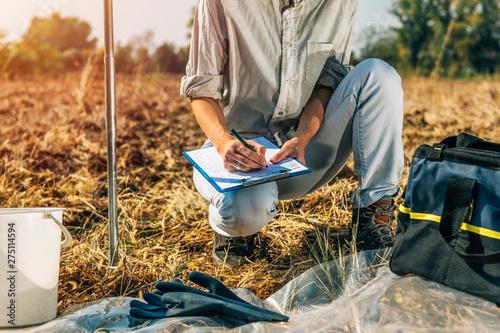 Fototapeta Soil Testing. Female Agronomists Taking Notes Outdoor